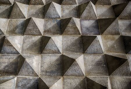 architectural  detail: A section of an exterior wall shows an architectural detail of pyramids carbed in stone in a repeating geometric pattern. Stock Photo