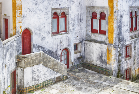 craked: A small interior courtyard of one of the historic buildings in Sintra, Portugal is a quiet spot to reflect on elements of the Moorish influence on the architeture. The building shows some signs of direpair with craked walls and faded paint.