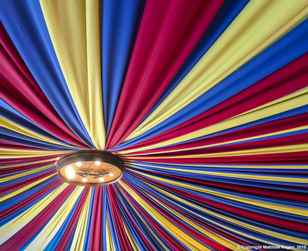 light fixture: A colorful canopy of red, yellow and blue curtains radiate from a light fixture in a ceiling.