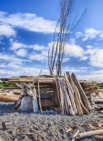cloud drift: A small homemade structure with an entrance, built out of driftwood on a beach in Puget Sound, provides shelter from the wind. Stock Photo