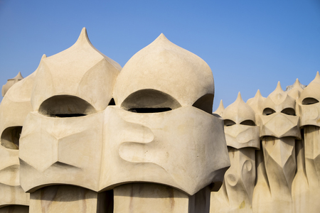 antoni: BARCELONA, SPAIN - APRIL 20. 2015: A series of chimneys on the roof of Casa Mila in Barcelona resemble soldiers in helmets. The building was designed by Antoni Gaudi.
