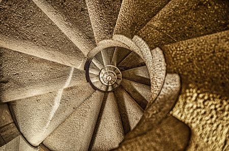 A view looking upwards through the center of a long spiral staircase in a Barcelona cathedral.