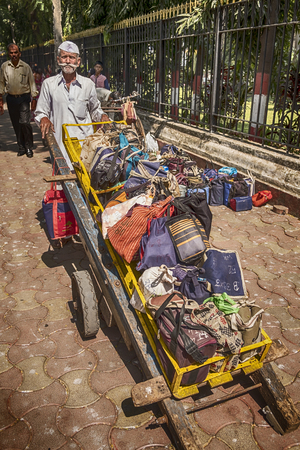 delivers: MUMBAI, INDIA - NOVEMBER 10, 2016: In Mumbai, a well-known logistics system delivers lunches through the streets. A dabbawala, or lunchbox delivery worker, located just outside the Mumbai train station has a full handcart of lunches ready to deliver.