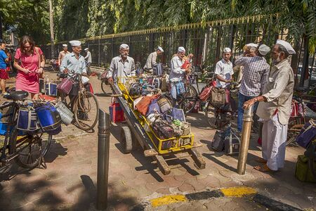 MUMBAI, INDIA - NOVEMBER 10, 2016: In Mumbai, a well-known logistics system delivers lunches through the streets. A dabawalah with a fully loaded hand cart sets off on his journey to deliver lunches from the Mumbai train station to offices and shops throu