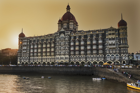 MUMBAI, INDIA - NOVEMBER 12: A view of the Taj Palace at sunset looking over part of the harbor in front of the promenade in Mumbai, India. Editorial