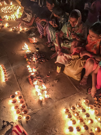 illuminate: VARANASI, INDIA - NOVEMBER 14, 2016: On the night of Dev Diwali in Varanasi, Hindu women light candles  to illuminate the festival while sitting on the steps of a ghat on the Ganges River in Varanasi.