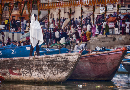 bathers: VARANASI, INDIA - NOVEMBER 15, 2016: On the morning after the Dev Diwali festical, an anonymous young man is wrapped in a blanked on a boat near one of the ghats with bathers on the Ganges River in Varanasi.