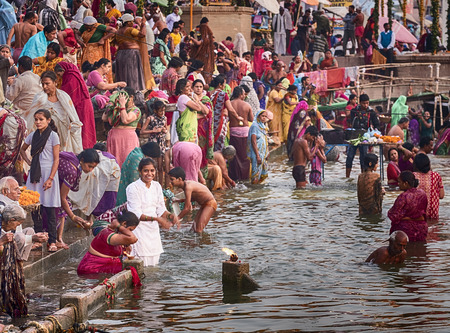VARANASI, INDIA - NOVEMBER 15, 2016: On the morning after the Dev Diwali festival, an anonymous young woman in white bathes in the holy waters of the Ganges River amid a crowd on steps of a ghat on the Ganges River in Varanasi. Editorial