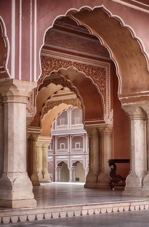 building structures: JAIPUR, INDIA - NOVEMBER 18, 2016: A series of arches leads through the central pavilion of the City Palace in Jaipur, India.