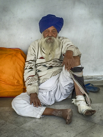 DELHI, INDIA - NOVEMBER 20, 2016: An anonymous elderly Sikh gentleman is waiting in a hallway outside the Gurudwara Bangla Sahib Sikh Temple in Delhi, India while waiting for medical attention for his feet and legs.