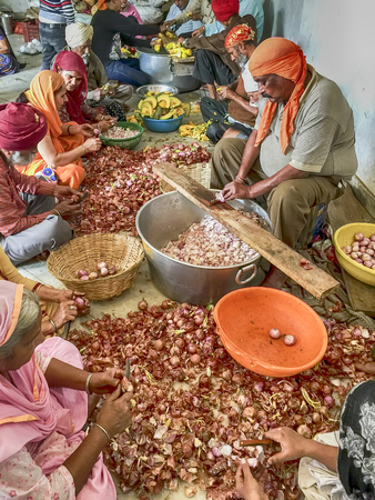 gurudwara: DELHI, INDIA - NOVEMBER 20, 2016: A group of volunteers is chopping garlic to prepare for the free community dining in the Langar Hall at the Gurudwara Bangla Sahib shrine in Delhi, India. Editorial