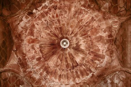 The ceiling of one of the smaller domes shows the pattern of red sandstone used in the building. A single light in the center provdes some illumination.