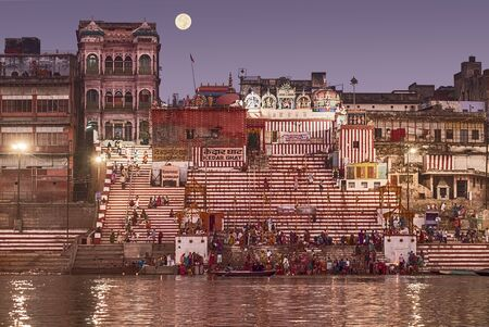 A crowd of people bathing in the Ganges River before the sun comes up on the day after Dev Diwali. The moon is in the super moon phase.