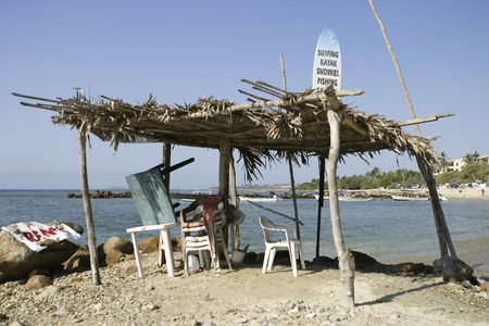ramshackle: A ramshackle beach shack or lean-to in the tropics with an advertising sign on the surfboard sticking up through the roof. This casual sales office provides minimum shelter from the elements as well as a location for a surfing, snorkeling, and watersports