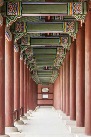 ornately: A colonnade at the Geunjeongmun Gate (or third gate) of the Gyeongbokgung Palace complex in Seoul, Korea shows the row of red columns topped by ornately painted wood beams.
