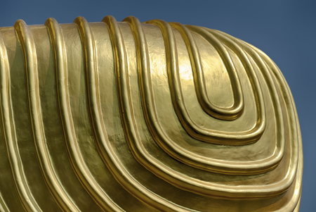 A detail of the shapes on Buddhas knee is highlighted against a blue sky at the Golden Temple religious complext at Dambulla near Kandalarma in Sri Lanka. Stock Photo