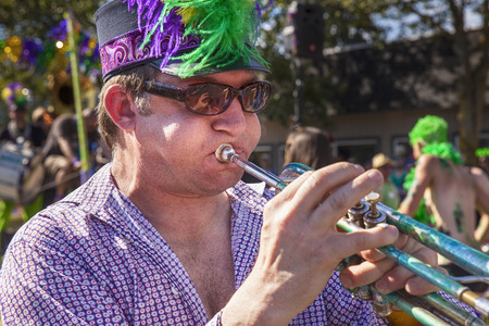 SEATTLE, WA - JUNE 22, 2013: An unidentified musician with a feathered cap and sunglasses plays a trumpet as part of Honkfest in the Fremont Summer Solstice Parade in Seattle.