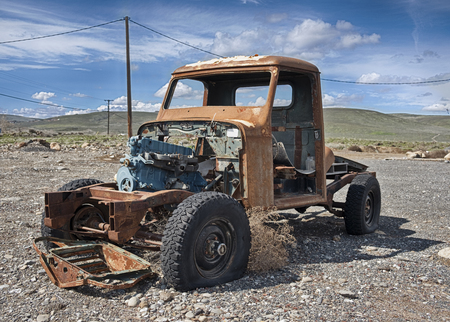 A solitary old pickup truck, abandoned in a gravel parking lot and exposed to the elements in Eastern Washington, is rusting while being scavenged for parts. Stock Photo