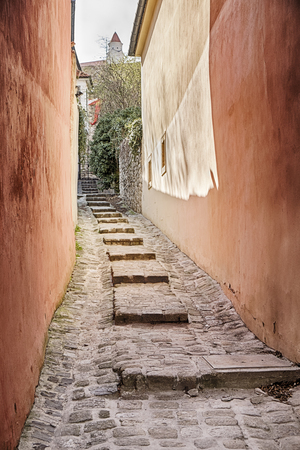 A narrow alley with stone steps climbs a hill leading towards the castle of Bratislava in Slovakia.