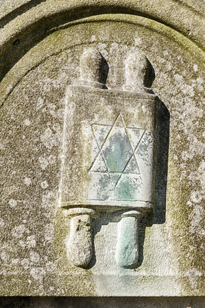 A decorative element showing a torah scroll on a gravestone marks the grave of a religous man in the Okopawa Street Jewish cemetery in Warsaw, Poland.