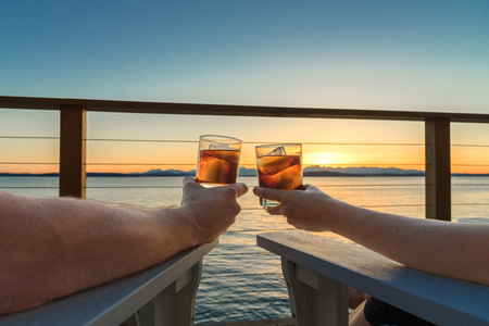 Couples arms holding up cocktails at sunset on seaside deck Stock Photo