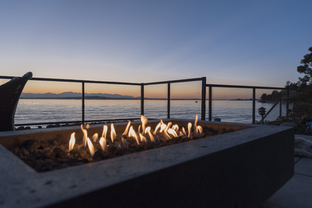 Fire pit gas lit by the sea at sunset