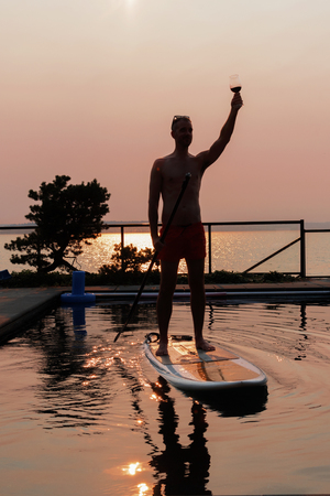 Wine at sunset in the pool Banco de Imagens - 74415827