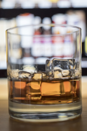 Close up view of whiskey in glass with ice