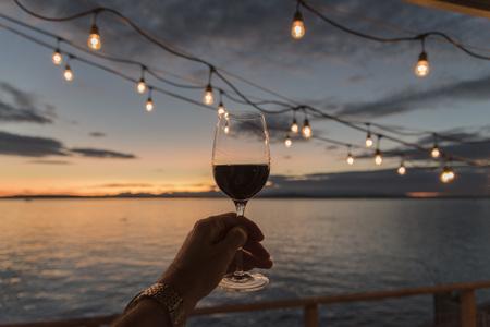 Holding wine up under deck lights at sunset Banco de Imagens - 87870732