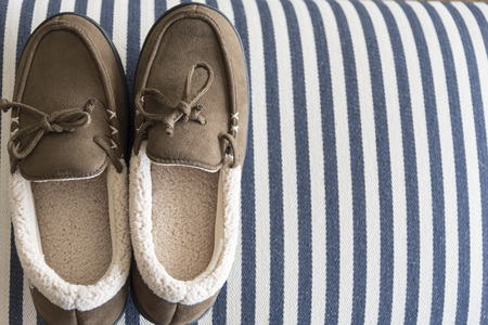 Slippers on striped fabric with copy space