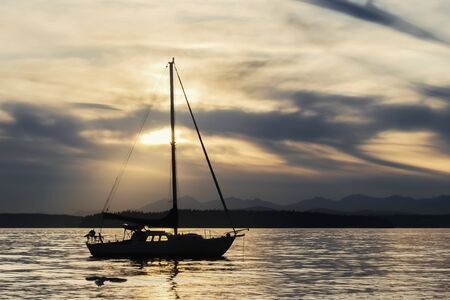 Silhouetted sailboat at sunset