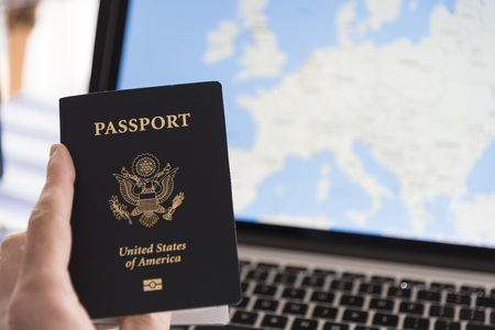 Passport in hand with computer showing map of Europe in background.