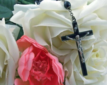 a rosary cross surrounded by silk roses