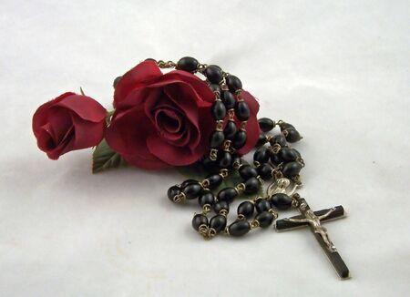 różaniec: jeden krzyż i paciorki różańca z czerwonym jedwabiem róże