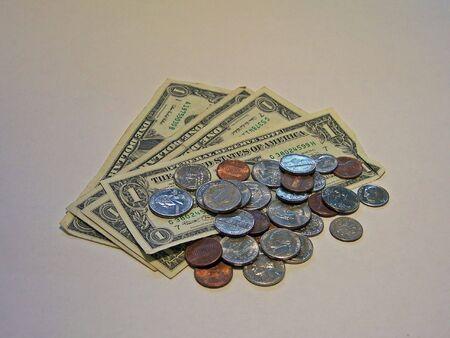 pile of change ontop of dollar bills