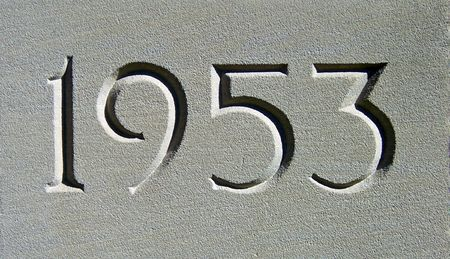date 1953 engraved in a gray cement  wall photo