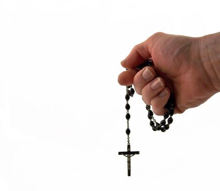 a rosary cross held in mans hand