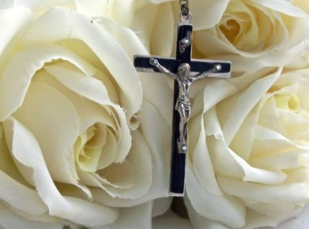doctrine: a rosary cross surrounded by white silk roses