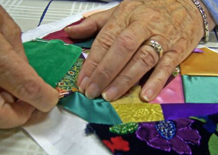 patchwork: womans hands stitching a crazy quilt together