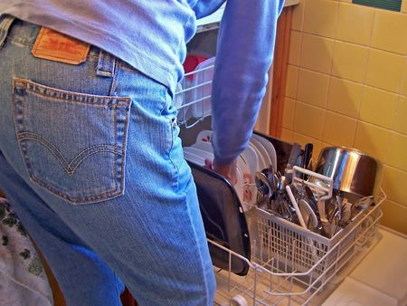 bending over: woman in jeans bending over loading diswasher