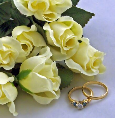 tender sentiment: wedding rings with silk yellow rose buds