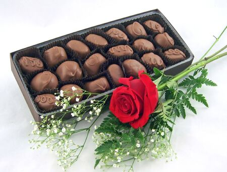 a box of chocolates with one red rose