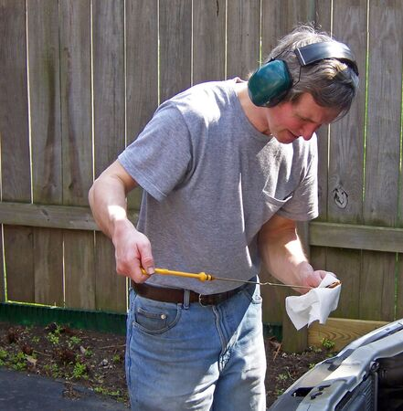 depth measurement: man working on car in home driveway Stock Photo