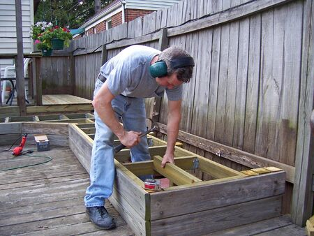 hammering: a man hammering working on backyard deck