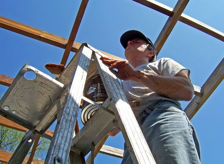 man staining exterior arbor deck at home Stock Photo