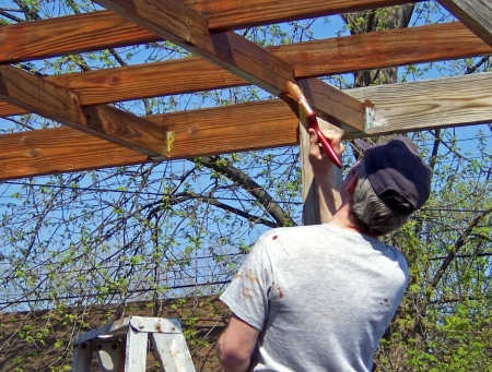 varnish: man staining exterior arbor deck at home Stock Photo