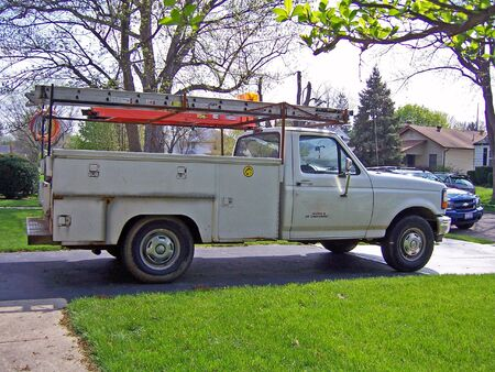 electric utility: white heating and air service truck parked at residence