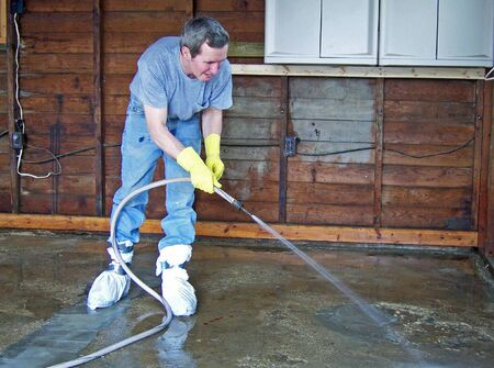man hosing inside of garage with water  Stock Photo