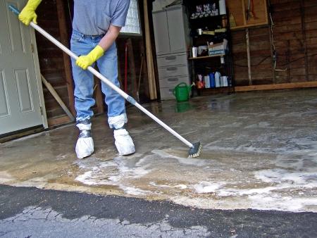 clean home: een man schoonmaak garage vloer met zeep