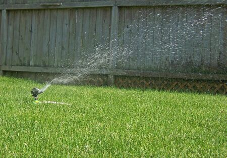 drench: sprinkler watering green lawn on summer day